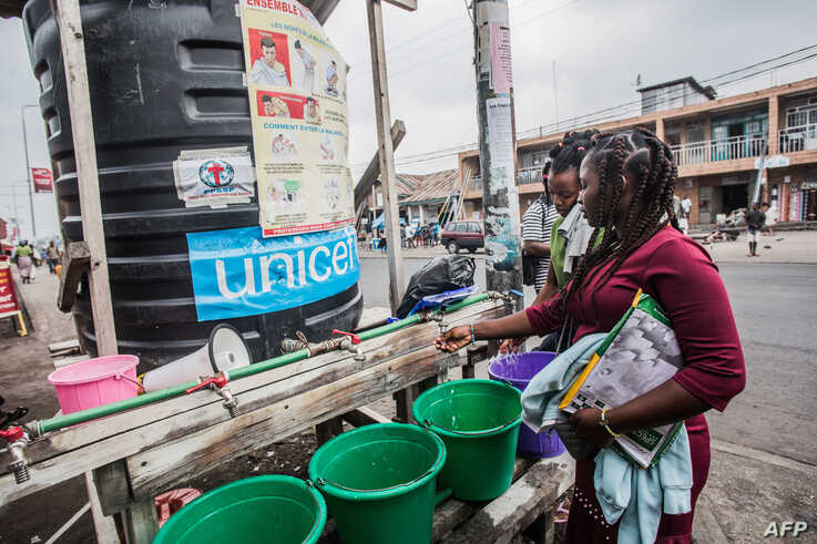 FILE - Women wash their hands in Goma, Democratic Republic of Congo, July 31, 2019.