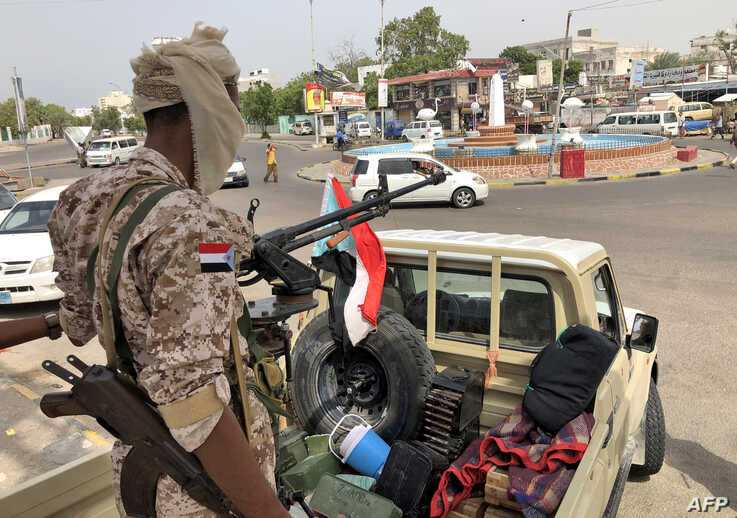 A fighter mans the turret of a pickup truck mounted with an anti-aircraft gun displaying the southern Yemeni separatist flag in Khor Maksar in the center of Aden, Yemen, Aug. 12, 2019.