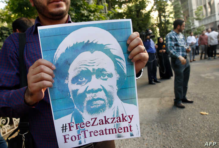 In this file photo taken on July 17, 201 Iranian and Nigerian students hold up posters of Nigerian Shiite cleric Ayatollah Ibrahim Zakzaky during a demonstration outside the Nigerian embassy in Tehran.