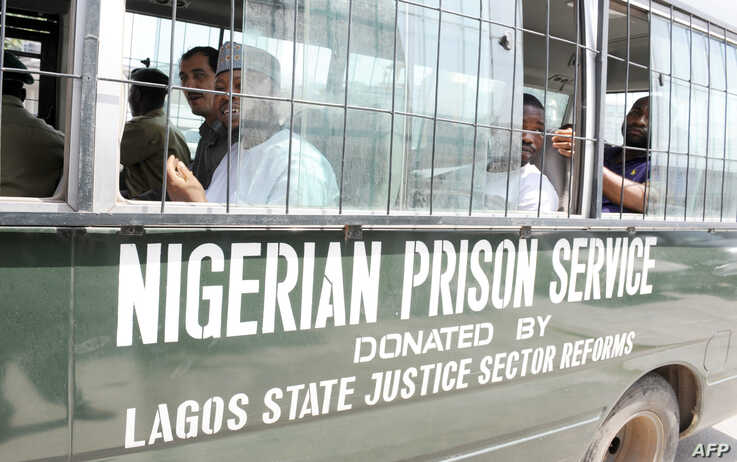 Suspects sit on a bus taking them to prison after a hearing at the Federal High Court in Lagos, March 7, 2011. The prison service is now called the Nigerian Correctional Service.