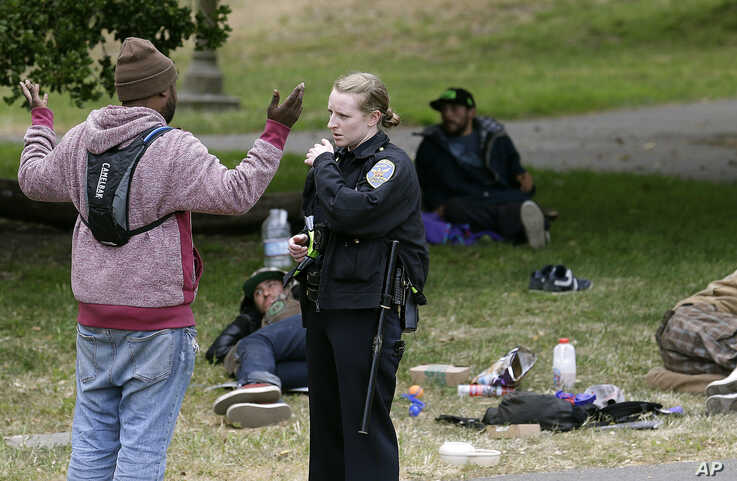 San Francisco Police Officer Kathleen Cavanaugh talks to a man, May 24, 2017, while patrolling Golden Gate Park in San Francisco. Courts around the country tried to ease the burden of fines and fees in the wake of riots in Ferguson, Mo., in 2014 that were blamed in part on a torrent of traffic and other minor citations that saddled people with debt and even sent them to jail.