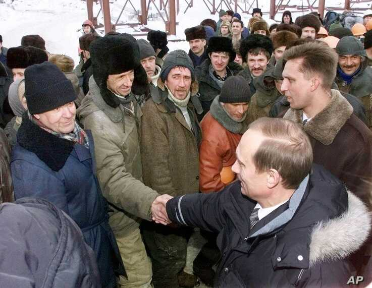 FILE - Acting President Vladimir Putin shakes hands with workers during his visit to an oil and gas field in Surgut, western Siberia, Russia, March 3, 2000.