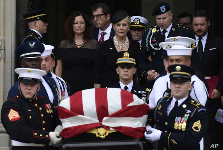 FILE - Cindy McCain, center, widow of Sen. John McCain, R-Ariz., escorted by her son Jimmy McCain and other family members, follows his casket as it is carried out of Washington National Cathedral in Washington, Sept. 1, 2018.