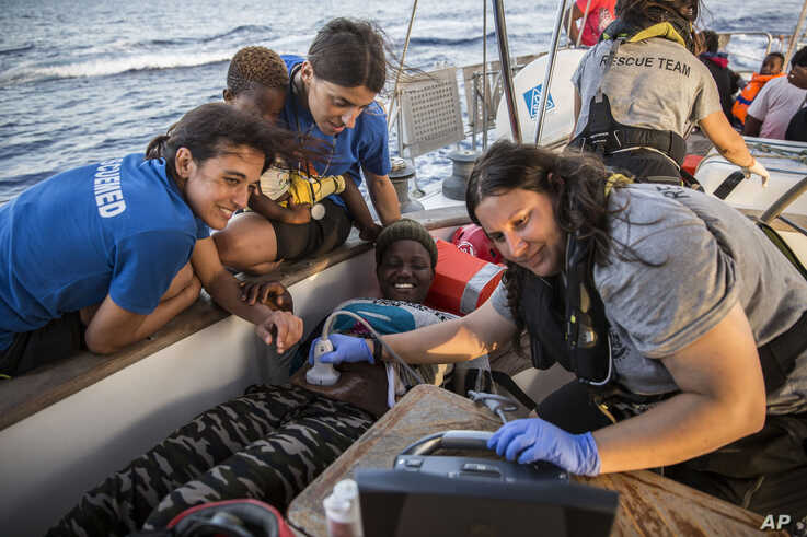 Doctors tend to a pregnant woman on a Mediterranea Saving Humans NGO boat, as they sail off Italy's southernmost island of Lampedusa, just outside Italian territorial waters, July 4, 2019.