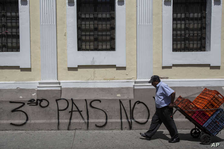 """A man carries boxes past the Spanish message: """"No third country"""" near Congress in Guatemala City, July 30, 2019."""