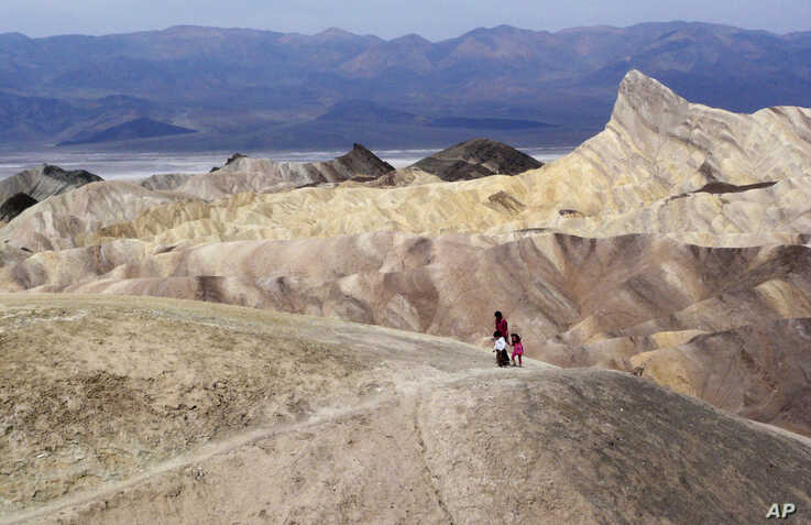 FILE - Tourists walk along a ridge at Death Valley National Park, Calif., April 11, 2010. A U.S. Navy fighter jet crashed July 31, 2019, in the national park, injuring several people who were at a scenic overlook.