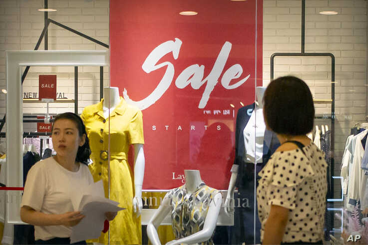 People walk past a store advertising a sale in a shopping mall in Beijing, Aug. 2, 2019.