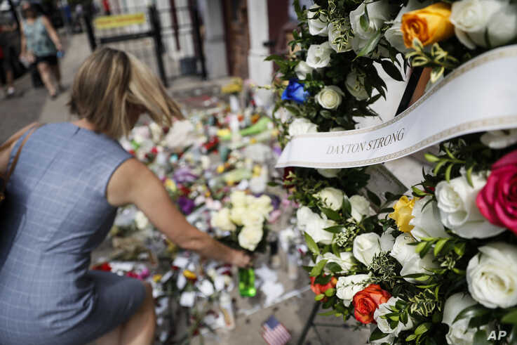 Mourners bring flowers to a makeshift memorial, Aug. 6, 2019, for the slain and injured in the Oregon District after a mass shooting that occurred Aug. 4, 2019, in Dayton, Ohio.