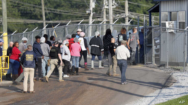 Workers exit a Koch Foods Inc. processing plant as U.S. immigration officials conducted a raid in Morton, Miss., Aug. 7, 2019.
