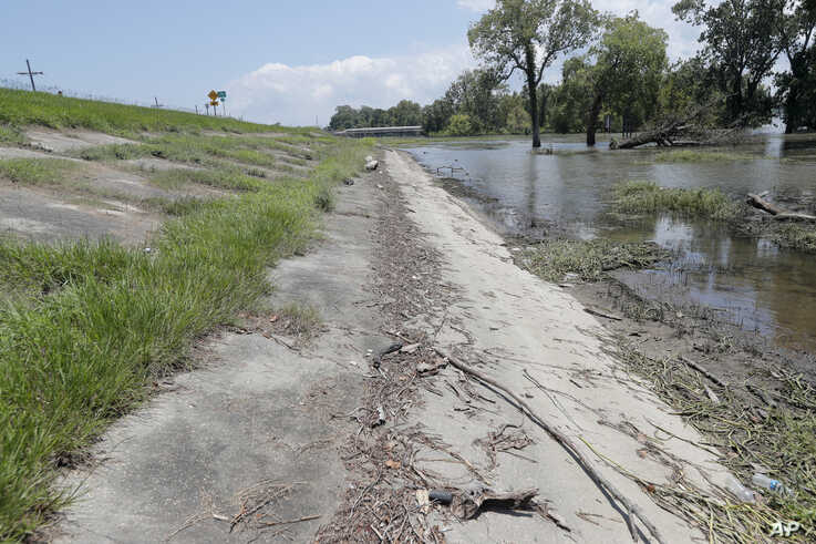 FILE - Water lines and receding water are seen on the backside of the Mississippi River levee in Norco, La., just upriver from New Orleans, July 25, 2019.