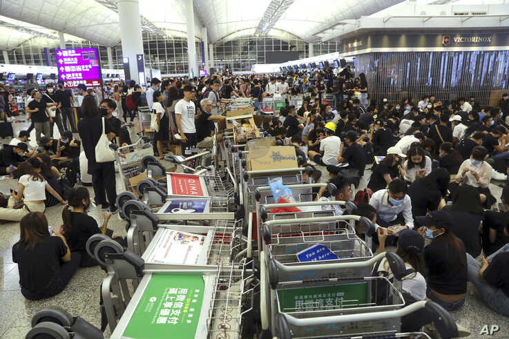 Protesters use luggage trolleys to block the walkway to the departure gates during a demonstration at the Airport in Hong Kong, Aug. 13, 2019.