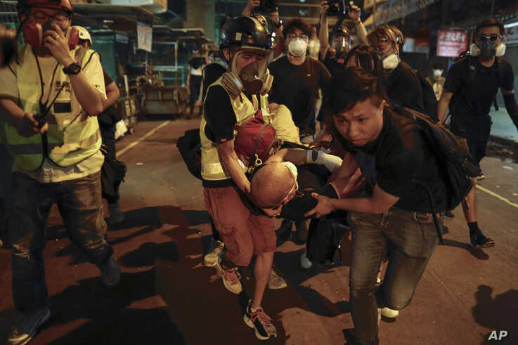Medical staffs and protesters carry an injured man as they confront with policemen near the Shum Shui Po police station in Hong Kong on  Aug. 14, 2019.