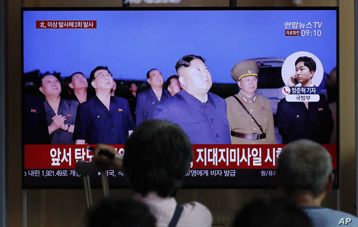 People watch a TV news program reporting about North Korea's firing projectiles with a file image of North Korean leader Kim Jong Un at the Seoul Railway Station in Seoul, South Korea, Aug. 16, 2019.