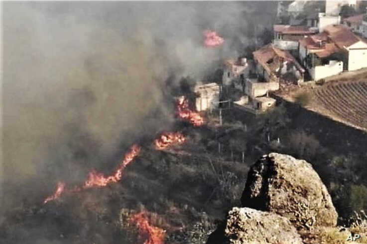 In this photo issued by Cabildo de Gran Canaria, flames from a forest fire burn close to houses in El Rincon, Tejeda on the Spanish Gran Canaria island on Sunday Aug. 18, 2019.