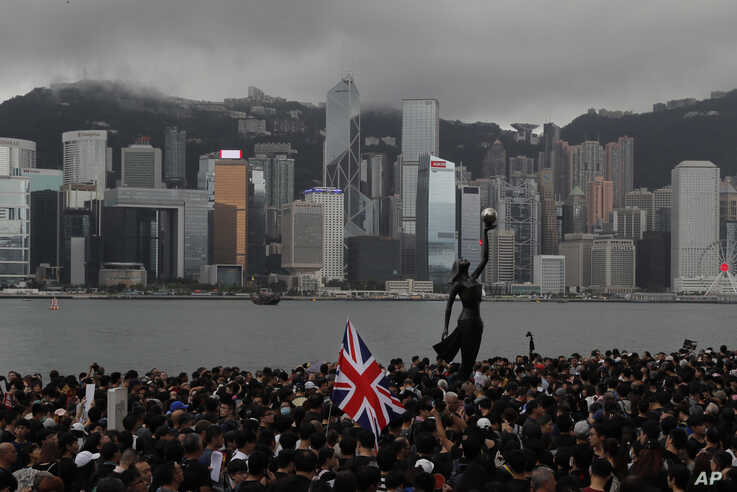 FILE - Protesters carrying the British flag march near the harbor of Hong Kong, July 7, 2019. Hong Kong police on Tuesday confirmed receiving a report about a British foreign ministry employee missing since crossing into China on a business trip.