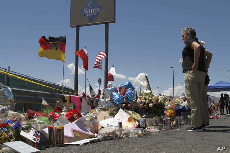 FILE - Mourners visit the makeshift memorial near the Walmart in El Paso, Texas, Aug. 12, 2019, where 22 people were killed in a mass shooting.