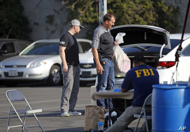 Federal agents work at a downtown Los Angeles parking lot after predawn raids Thursday, Aug. 22, 2019. U.S. authorities have uns