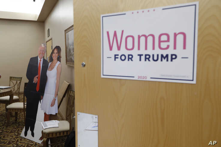 A cutout of President Trump and his wife Melania is shown outside a training session for Women for Trump, An Evening to Empower, in Troy, Mich., Aug. 22, 2019.