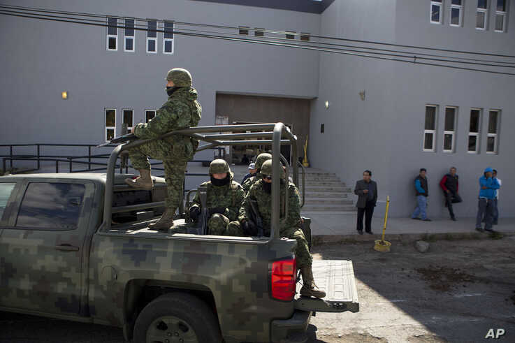 FILE - A military patrol drives past family members and funeral home workers waiting to pick up the bodies of people killed a day earlier in Apatzingan, outside the forensic morgue in Morelia, Michoacan, Mexico, Jan. 7, 2015.