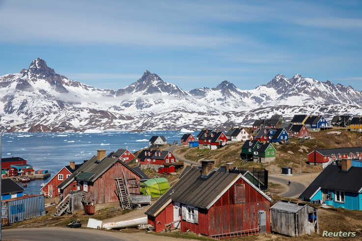FILE - Snow-covered mountains rise above the harbor and town of Tasiilaq, Greenland, Jan. 10, 2019.