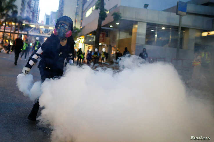 An anti-extradition bill protester throws a tear gas cartridge back at police during clashes in Wan Chai in Hong Kong, Aug. 11, 2019.