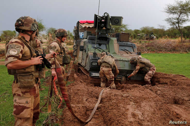 """French soldiers of the """"Belleface"""" Desert Tactical Group (GTD) try to move an all terrain armored vehicle from the mud in the Gourma region during Operation Barkhane in Ndaki, Mali, July 28, 2019."""