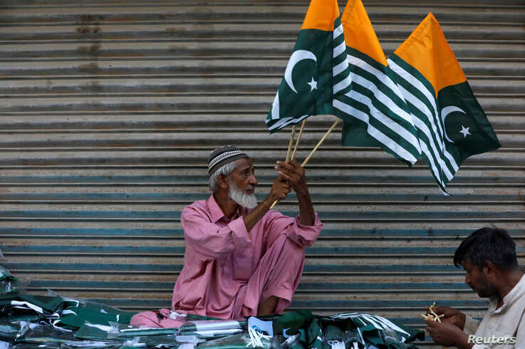 A man sells Kashmir's flags and patriotic memorabilia ahead of Pakistan's Independence Day, along a market in Karachi