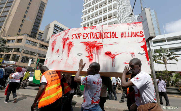 FILE - Members of the civil society carry a coffin stained with mock blood as they chant slogans during a protest dubbed 'Stop extrajudicial killings', in Nairobi, Kenya.