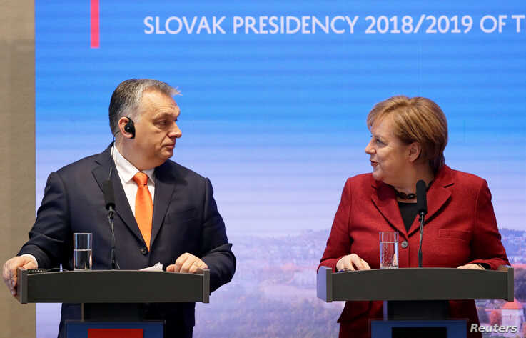FILE - German Chancellor Angela Merkel speaks to Hungarian Prime Minister Viktor Orban during a news conference in Bratislava, Slovakia, Feb. 7, 2019.