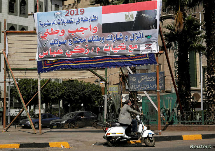 "A man drives his motorcycle in front of a banner reading in Arabic, ""Participation in constitutional amendments is a national duty"", in Cairo, Egypt April 3, 2019."