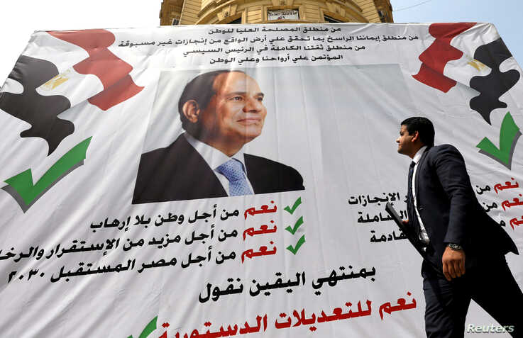 "A man walks in front of a banner reading, ""Yes to the constitutional amendments, for a better future"", with a photo of the Egyptian President Abdel Fattah al-Sisi before the referendum on constitutional amendments in Cairo, Egypt April 16, 2019."