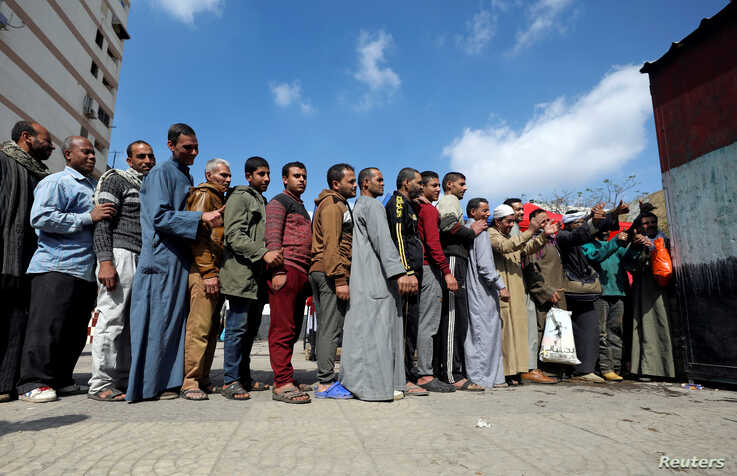 People stand in line to cast their vote during the referendum on draft constitutional amendments, at a polling station in Cairo, Egypt April 20, 2019.