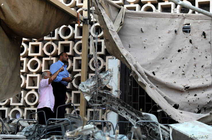 Egyptian investigators are seen in front of the damaged facade of the National Cancer Institute after an overnight fire from a blast, in Cairo, Egypt, Aug. 5, 2019.