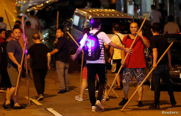 A man tries to prevent members of a group opposing anti-government protesters from clashing with people attending a demonstration in support of a city-wide strike and call for democratic reforms, Hong Kong, China, Aug. 5, 2019.