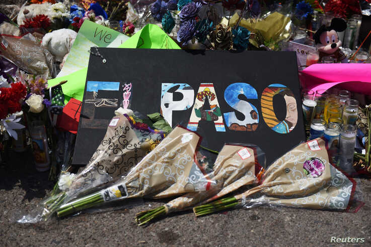 FILE - Flowers and candles are left at a memorial five days after a mass shooting at a Walmart store in El Paso, Texas, Aug. 8, 2019.