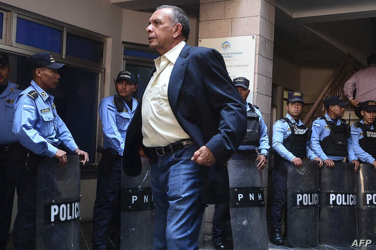 Close to police officers, Honduras' former president (2010-2014) Porfirio Lobo Sosa (front), waits outside a court before attending the hearing of his wife Rosa Elena Bonilla de Lobo -accused of misappropriation of public funds, illicit association and money laundering in Tegucigalpa, Honduras, Aug. 20, 2019.