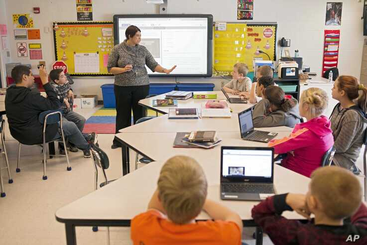 FILE -- Sixth-grade teacher Carrie Young guides her students through an exercise on their laptops as practice for the the Common Core State Standards Test in Stockport, Ohio, Feb. 12, 2015.