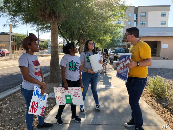 FILE - From left, Tameka Spence, Shelley Jackson, Karen Hernandez and Francisco Lopez talk following a demonstration where they and others voiced their opposition to a local city initiative, Aug. 20, 2019.