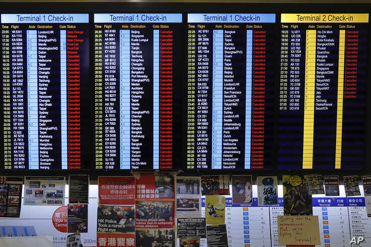Protest placards are placed as the flights information board shows the cancellation of outbound flights at the Hong Kong International Airport, Aug. 12, 2019.