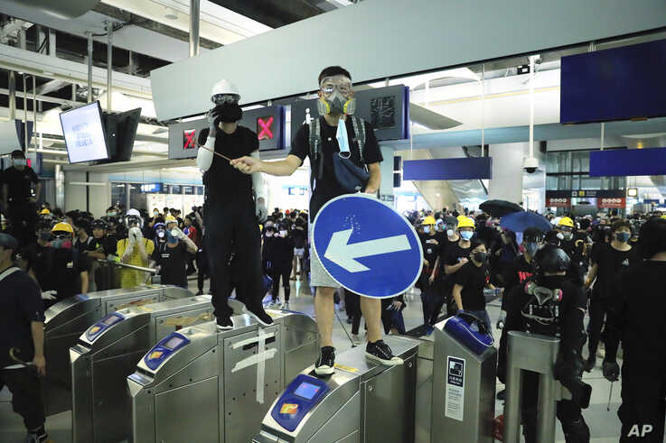 Demonstrators stand on turnstiles during a protest at the Yuen Long MTR station in Hong Kong, Aug. 21, 2019.