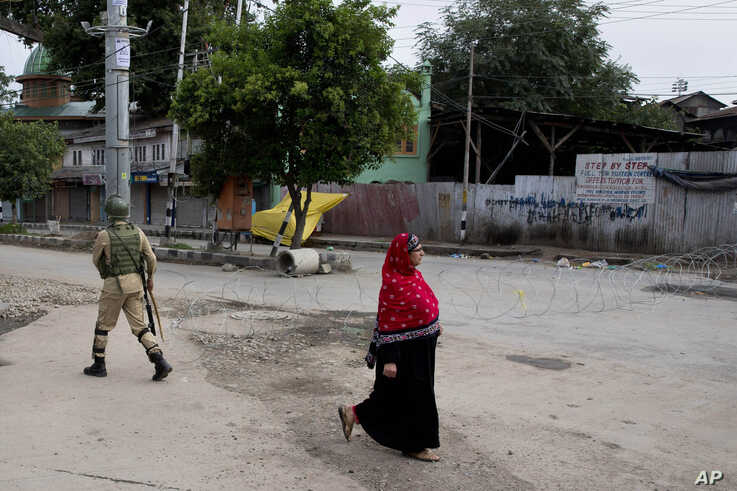 A woman walks past an Indian paramilitary soldier who prepares to block a road with barbed wires during security lockdown in Srinagar, Indian-controlled Kashmir, Aug. 18, 2019.