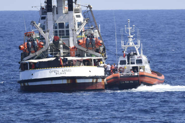 An Italian Coast Guard boat, right, approaches the Spanish humanitarian rescue ship Open Arms, off the Sicilian island of Lampedusa, southern Italy, Aug. 20, 2019.