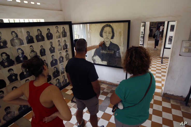 Visitors view portraits of victims executed by the Khmer Rouge regime, at the Tuol Sleng Genocide Museum in Phnom Penh, Cambodia, April 9, 2015.