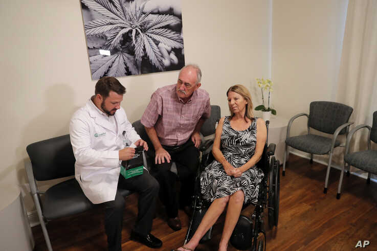 TJ Woodard, left, pharmacist in charge for Capitol Wellness Solutions, consults with Jeanette Anthony and her husband Albert Anthony, before he dispenses medical marijuana for Jeanette, a brain cancer patient, in Baton Rouge, Louisiana, Aug. 6, 2019.