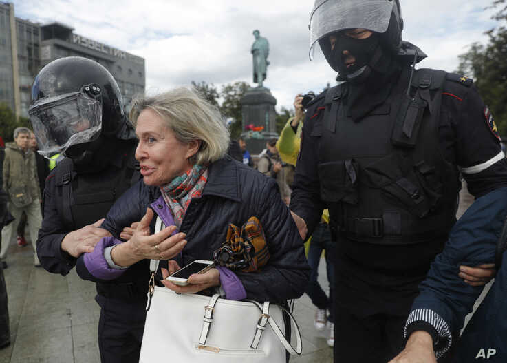 Police officers detain a woman during an unsanctioned rally in the center of Moscow, Russia, Aug. 3, 2019.