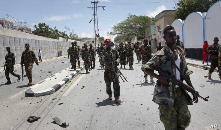 Somali government soldiers patrol following a blast near the presidential palace in the capital Mogadishu, Somalia, Aug. 30, 2016.
