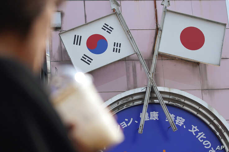 FILE - A woman walks past an advertisement featuring Japanese and South Korean flags at a shop in the Shin Okubo area in Tokyo, Japan, Aug. 2, 2019.