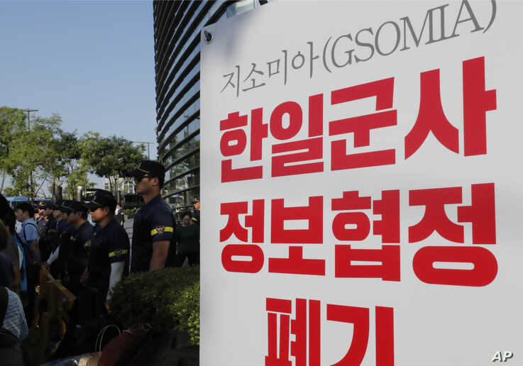 South Korean police officers stand near a banner during a rally demanding the South Korean government cancel the General Security of Military Information Agreement (GSOMIA) with Japan, in front of the Japanese embassy in Seoul, South Korea, Aug. 22, 2019.