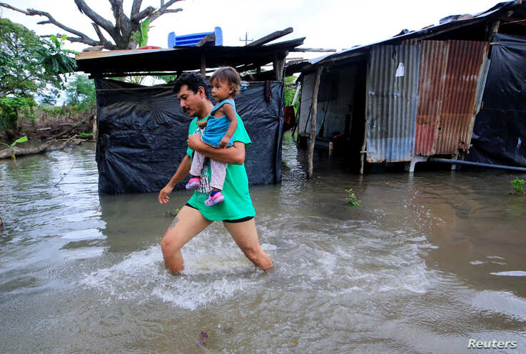 A local resident holding his daughter, walks through floodwaters after heavy rains in Malacatoya town, Nicaragua, Oct. 9, 2018.