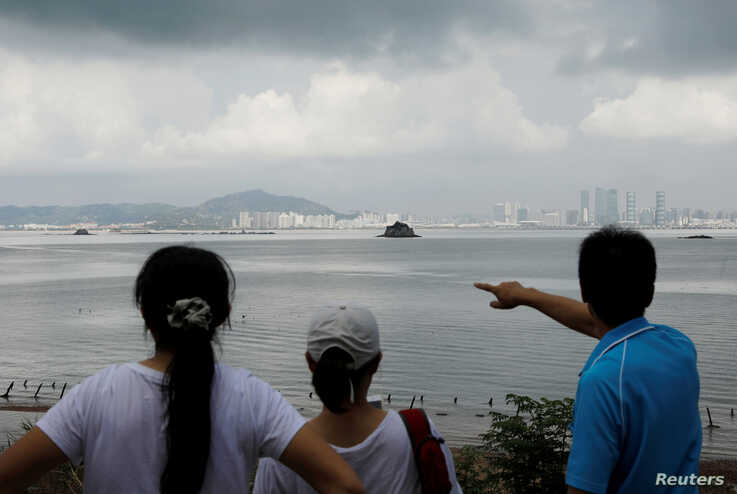 FILE- A tourist points at China's Xiamen from a former military fort on Lieyu island in Kinmen county, Taiwan, Aug. 20, 2018.